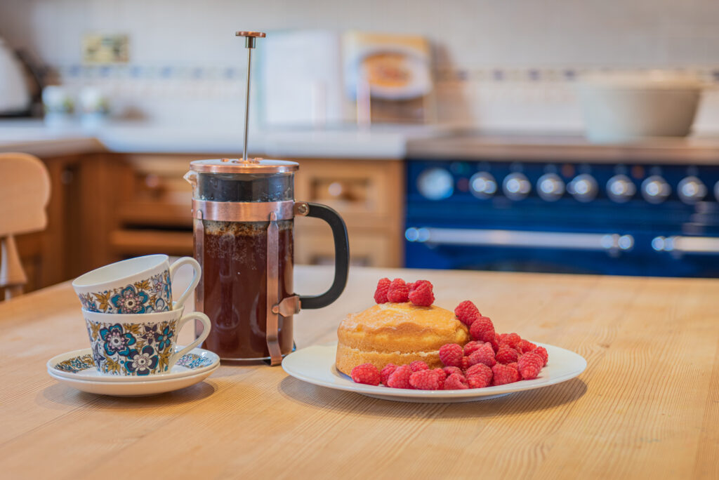 cafetiere filled with coffee, next to  floral teacups and victoria sponge cake with raspberries on table in kitchen