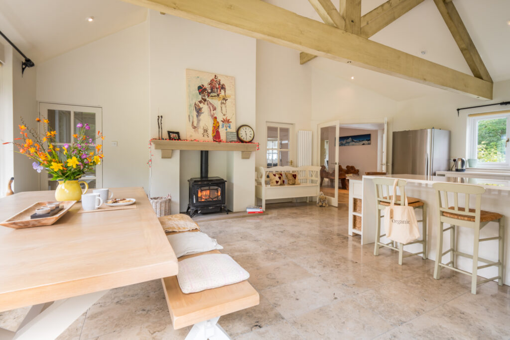 bright and light large kitchen space with large beams across room. Large pale wood dining table and bench in one corner, and breakfast bar in the opposite corner