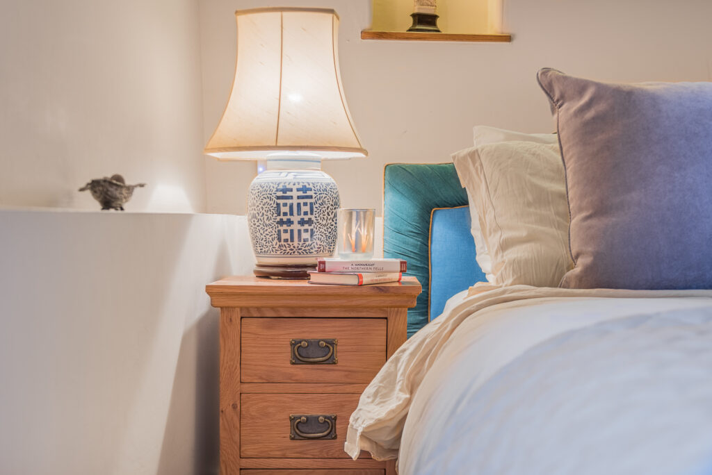 Dark wooden bedside table with blue cross patterned lamp and a couple of wainwright fell walking books with a candle placed on top