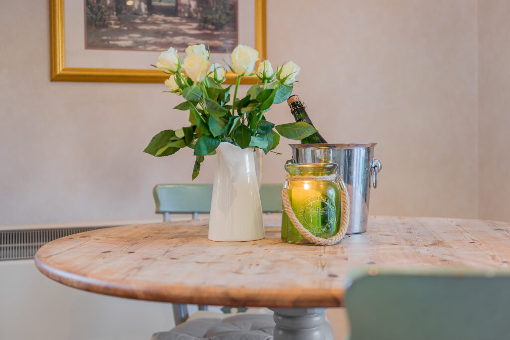 White roses in white jug and a green jar and candle in on wooden dining room table
