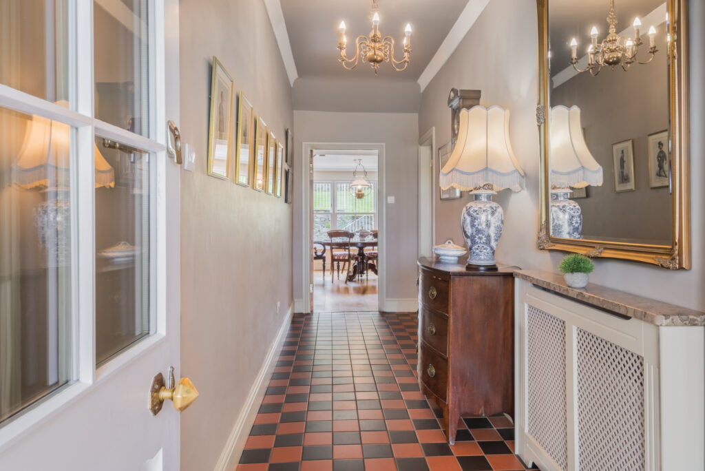A brightly lit entrance hallway of a home with brown and black tiled floor
