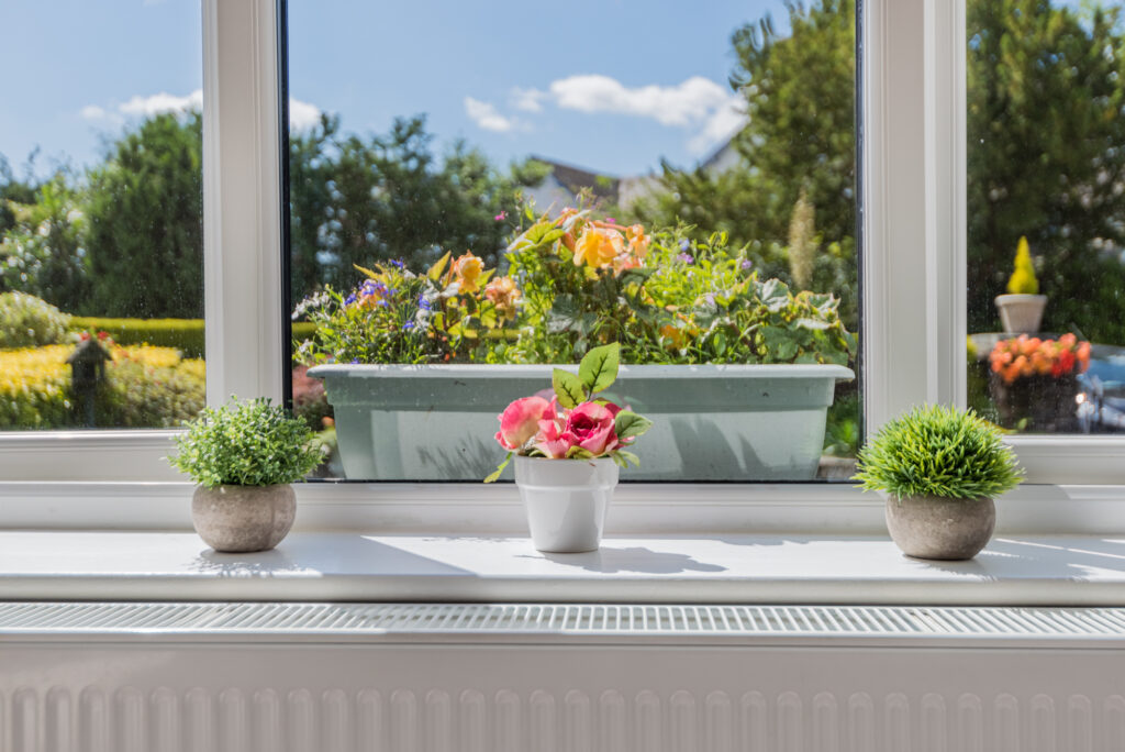 Brightly coloured flowers in pots on a windowsill, overlooking a large pot of flowers outside