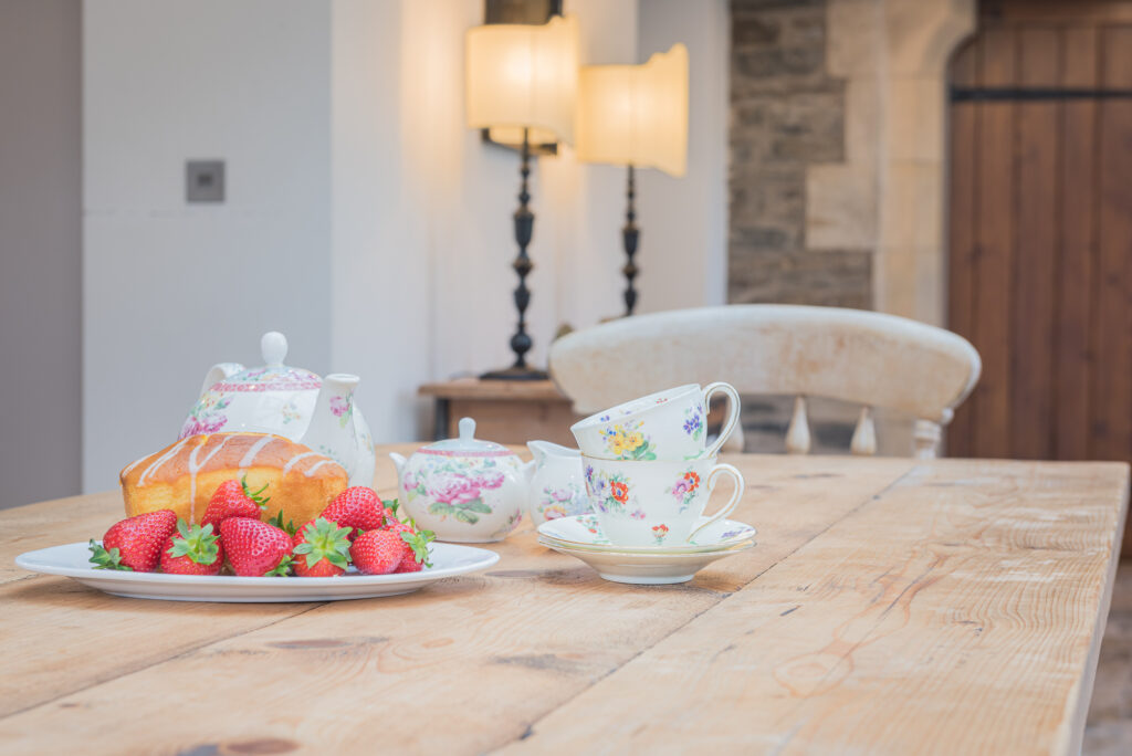 flowery teacup and saucer with sponge caked and strawberries on wooden dining table