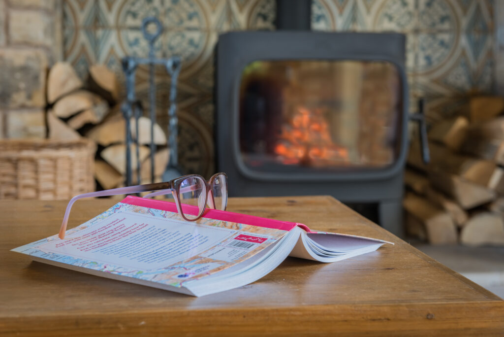 Face-down open book with glasses sitting on spine of book, placed on wooden coffee table in front of a lit fireplace