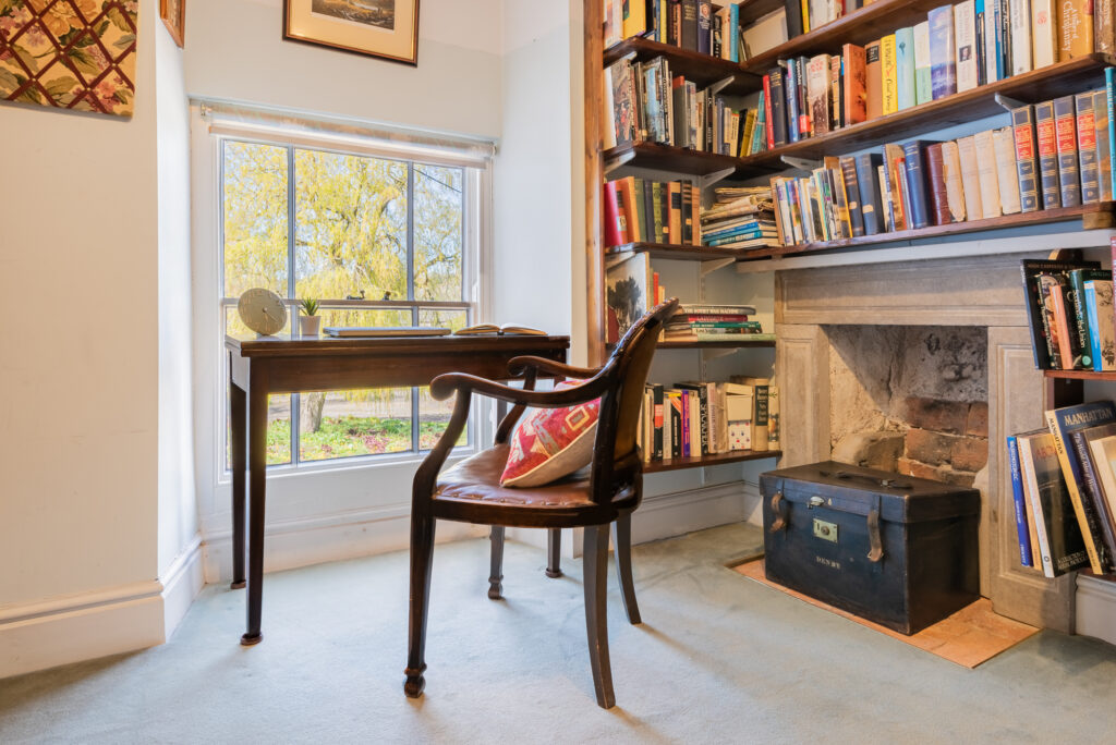 brightly, natural lit office space with dark wooden desk and chair placed in front of window overlooking garden, surrounded by bookshelves full of books