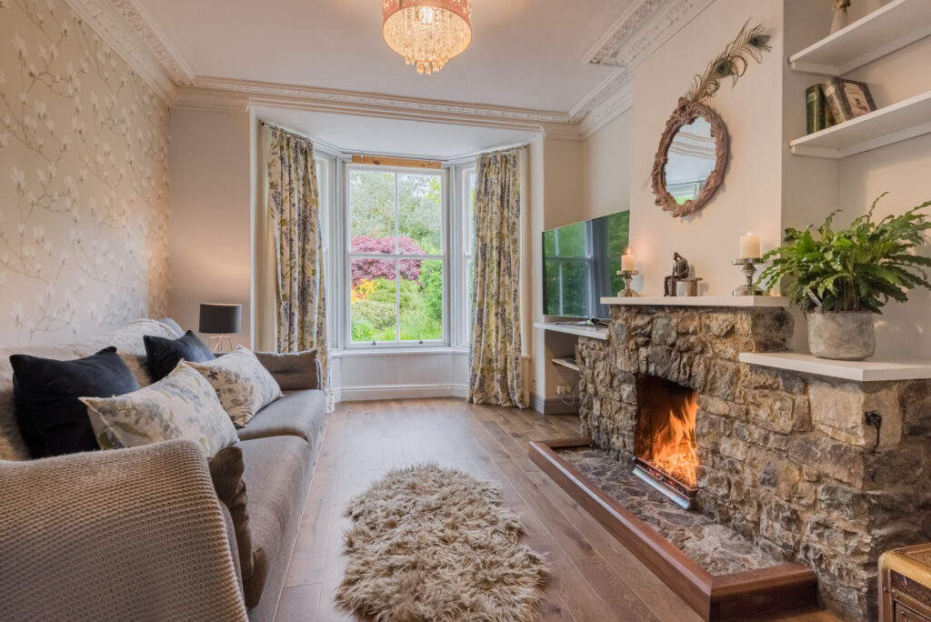 grey sofa accessorised with dark navy cushions, and white with blue flowered patterned cushions on left side of room, looking onto a brightly lit stone fireplace on right side of room
