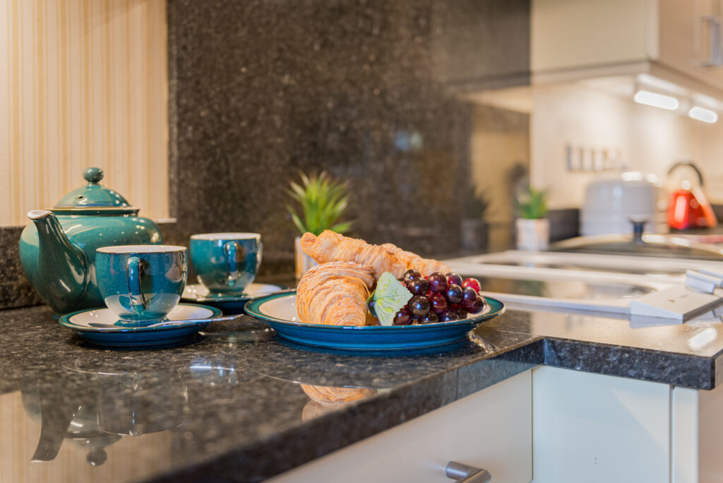 Grapes and croissants placed next to bright teal coloured teacups and teapot on dark grey marbled kitchen work surface