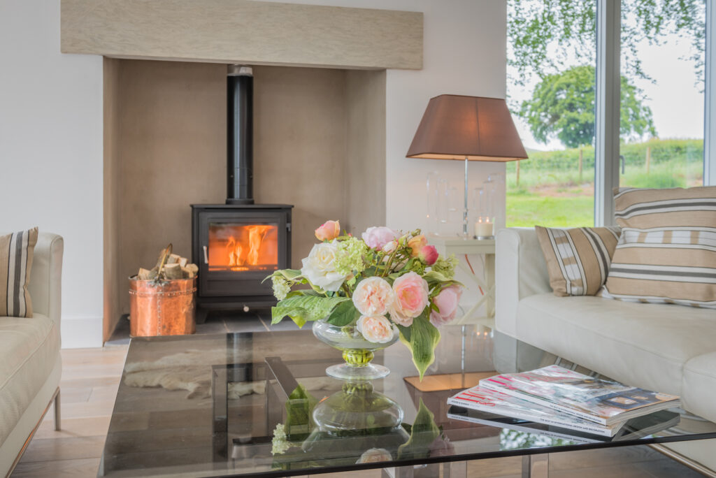 Beautiful pale pink rose in clear vase, sitting on glass table in centre of living room, in front of well-lit log burner