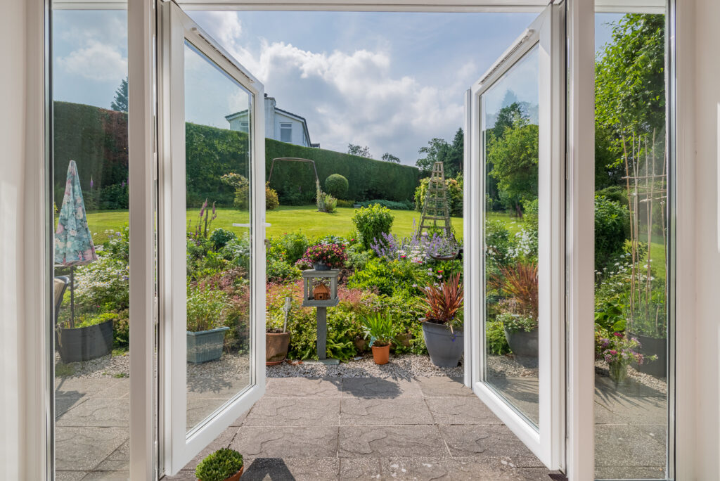 Open patio doors overlooking beautiful blue skies and brightly coloured flowers surrounding freshly cut garden space