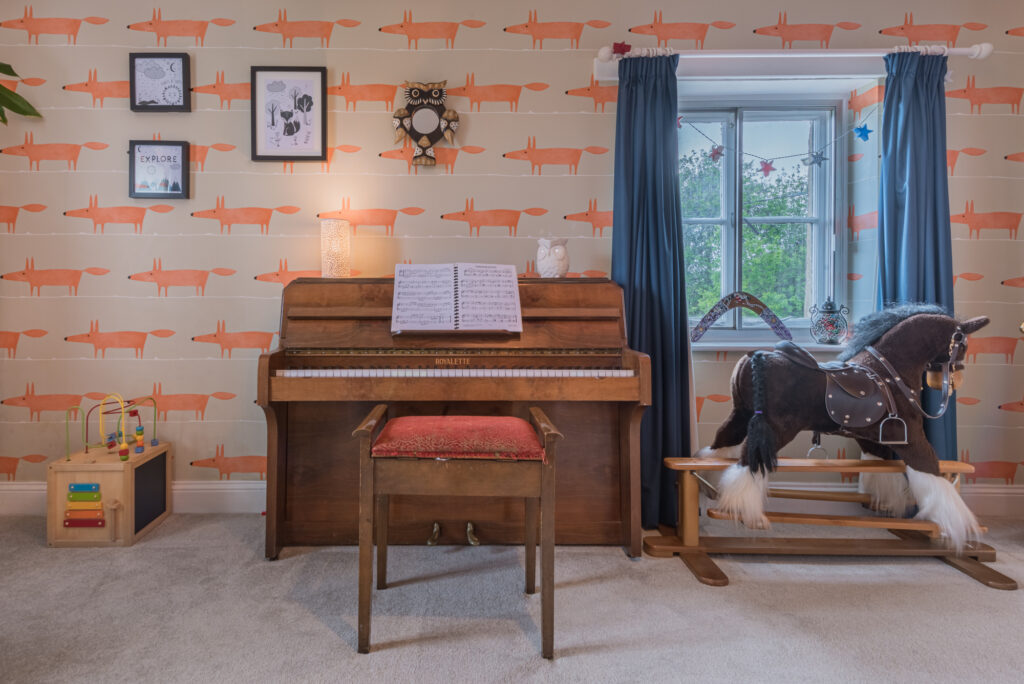 Piano and rocking horse sitting in kids room with grey and orange fox wallpaper