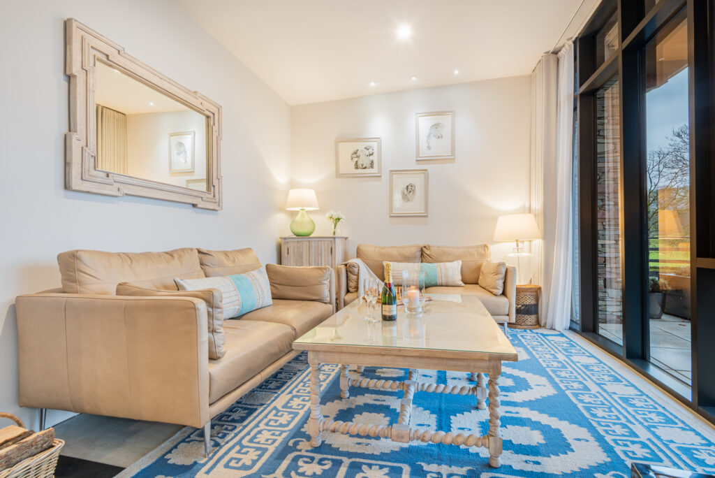 brightly lit living room, with light brown coloured sofas and coffee table sitting on bright blue and cream carpet