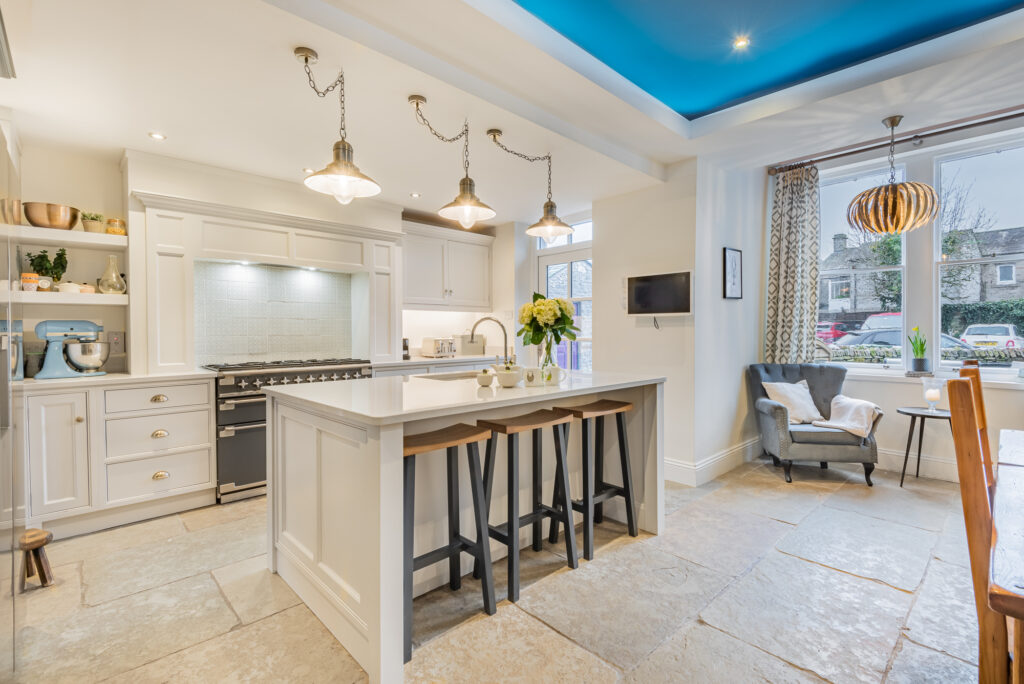 white and spacious kitchen, brightly lit by overhead lighting above large white kitchen island in middle of room