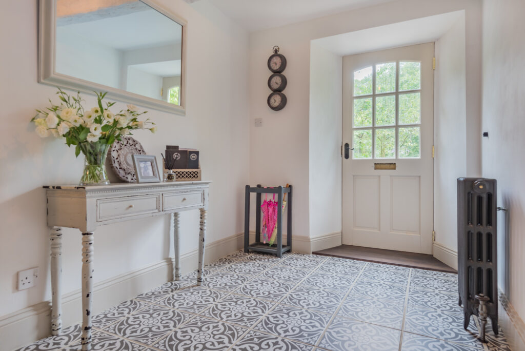 White hallway looking at inside of front door and dark blue patterned tiled flooring, with beautiful white flowers on cream side table
